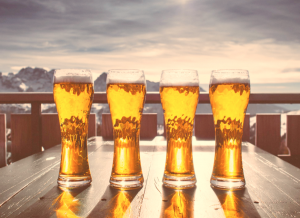 four beer glasses on outdoor table